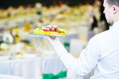 Servicio del evento del abastecimiento Mano del camarero con la comida Fotografía de archivo