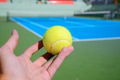 Servicio del jugador de tenis una pelota de tenis Fotografía de archivo