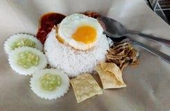 Servicio del lemak de Nasi con el huevo frito foto de archivo