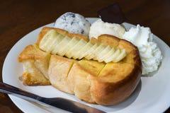 Servicio del pan de la tostada de la miel con el plátano, el helado y la crema azotada Fotos de archivo libres de regalías