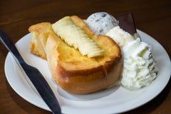 Servicio del pan de la tostada de la miel con el plátano, el helado y la crema azotada Fotografía de archivo libre de regalías