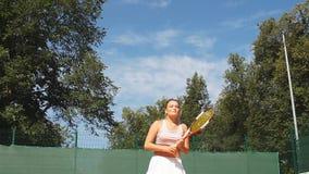 Servicio femenino hermoso del jugador de tenis al aire libre almacen de video
