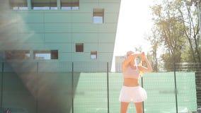 Servicio femenino hermoso del jugador de tenis al aire libre metrajes