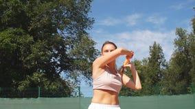 Servicio femenino hermoso del jugador de tenis al aire libre almacen de metraje de vídeo