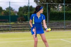 Servicio femenino hermoso del jugador de tenis al aire libre Foto de archivo libre de regalías