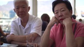 Servicio que espera de los pares mayores asiáticos para en el restaurante en Cape Town metrajes