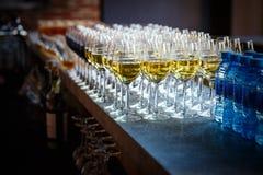 Servicios del abastecimiento los vidrios con el vino en fondo de la fila en el restaurante van de fiesta Imágenes de archivo libres de regalías