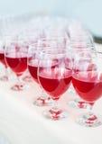 Servicios del abastecimiento los vidrios con el vino en fondo de la fila en el restaurante van de fiesta Imagenes de archivo