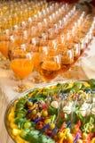 Servicios del abastecimiento los vidrios con el vino en fondo de la fila en el restaurante van de fiesta Foto de archivo libre de regalías