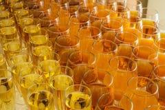 Servicios del abastecimiento los vidrios con el vino en fondo de la fila en el restaurante van de fiesta Fotos de archivo