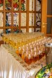 Servicios del abastecimiento los vidrios con el vino en fondo de la fila en el restaurante van de fiesta Imagen de archivo libre de regalías