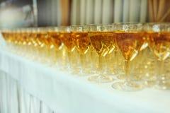 Servicios del abastecimiento vidrios con el vino en fondo de la fila en el partido Imagenes de archivo