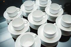 Servido con las tazas y los platillos en la tabla Fotografía de archivo