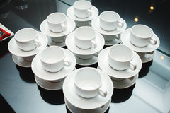 Servido con las tazas y los platillos en la tabla Imagen de archivo libre de regalías
