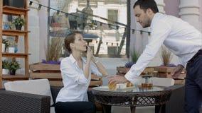 Servidor del camarero en el funcionamiento de la tabla, mientras que teléfono celular de la mujer que habla fotos de archivo libres de regalías
