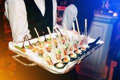 Servidor que guarda uma bandeja de aperitivos no banquete fotografia de stock royalty free