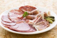 Servierplatte des unterschiedlichen Schinkenfleisches, -salami und -essiggurke Stockbilder