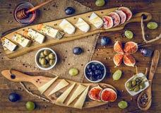 Servierplatte von italienischen Käsen mit Feigen, Oliven, Trauben und Honig Lizenzfreie Stockbilder