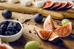 Servierplatte von italienischen Käsen mit Feigen, Oliven, Trauben und Honig Stockfotos