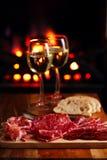 Servierplatte von serrano jamon kurierte Fleisch mit gemütlichem Kamin und Wein Lizenzfreie Stockbilder