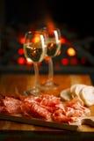 Servierplatte von serrano jamon kurierte Fleisch mit gemütlichem Kamin und Wein Stockfotografie