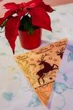 Serviette à côté d'usine rouge de poinsetta de feuille sur la table Images stock