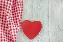 Serviette à carreaux et coeur en bois rouge Photos stock