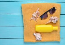 Serviette avec la protection solaire, coquilles de coque, lunettes de soleil sur les conseils en bois bleus Le concept des vacanc photos stock