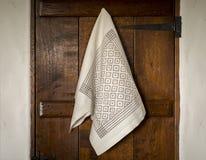 Serviette blanche avec le modèle d'oeil de Gray Bird accrochant sur la porte photographie stock