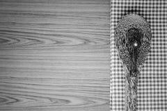 Serviette de cuisine avec la cuillère sur le colo noir et blanc de fond en bois photographie stock libre de droits