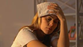 Serviette de participation de jeune femme sur le front, se sentant malade, symptôme de virus de grippe, épidémie banque de vidéos