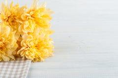 Serviette de table à carreaux avec les fleurs jaunes Photographie stock