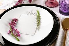 Serviette des Gedecks mit Sahne Farb, leere Karte und lila Blumendekor Stockfoto