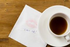 Serviette mit einem Kuss und einer Kaffeetasse auf hölzernem Hintergrund lizenzfreie stockfotografie