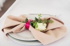 Serviette mit stieg Platzieren Sie BouquetBride der Braut und pflegen Sie Tabelle mit Blumenstrauß der Braut am Hochzeitsempfang  Lizenzfreie Stockfotografie