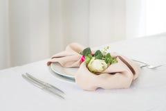 Serviette mit stieg Platzieren Sie BouquetBride der Braut und pflegen Sie Tabelle mit Blumenstrauß der Braut am Hochzeitsempfang  Lizenzfreies Stockbild