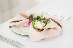 Serviette mit stieg Platzieren Sie BouquetBride der Braut und pflegen Sie Tabelle mit Blumenstrauß der Braut am Hochzeitsempfang  Lizenzfreie Stockfotos