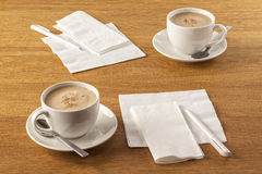 Serviette and Pen. Napkins or serviettes and pens on table, ready to make a note of your latest great ideas, along with a cup of coffee. Focus on paper Royalty Free Stock Photography