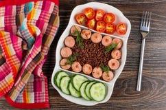 Serviette, plat divisé avec les saucisses frites, riz rouge, concombres, tomate, fourchette sur la table Vue supérieure photographie stock libre de droits