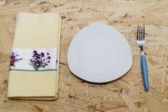 Serviette, plat et fourchette de plan rapproché sur la table Images libres de droits