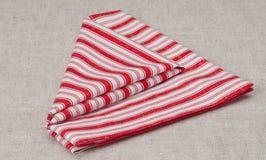 Serviette pliée par blanc rouge sur le fond de toile naturel Photo stock