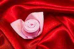 Serviette pliée sous forme de fleur rose Sur un tissu rouge Image stock