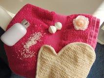 Serviette rose sur la baignoire avec le gant de bain photographie stock libre de droits