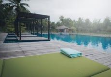 Serviette verte sur le lit du soleil près de la piscine photo libre de droits