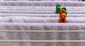 Serviettes blanches accrochant sur le dessiccateur avec les goujons de toile colorés images libres de droits