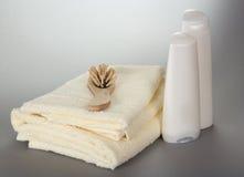 Serviettes, brosse à cheveux et bouteilles avec des cosmétiques Images stock