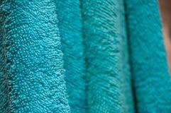 Serviettes de bain sèches onduleuses d'aigue-marine de couleur accrochant dans la salle de bains Photo libre de droits