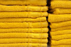 Serviettes de Bath de couleurs lumineuses dans une rangée dans une rangée sur le compteur d'un compteur de magasin Vente Photographie stock libre de droits