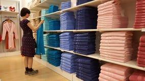 Serviettes de examen de belle femme de brune dans un magasin à Eskisehir Image stock
