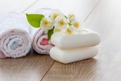 Serviettes et savon blancs pour des procédures de salle de bains et des fleurs des jas Photo libre de droits
